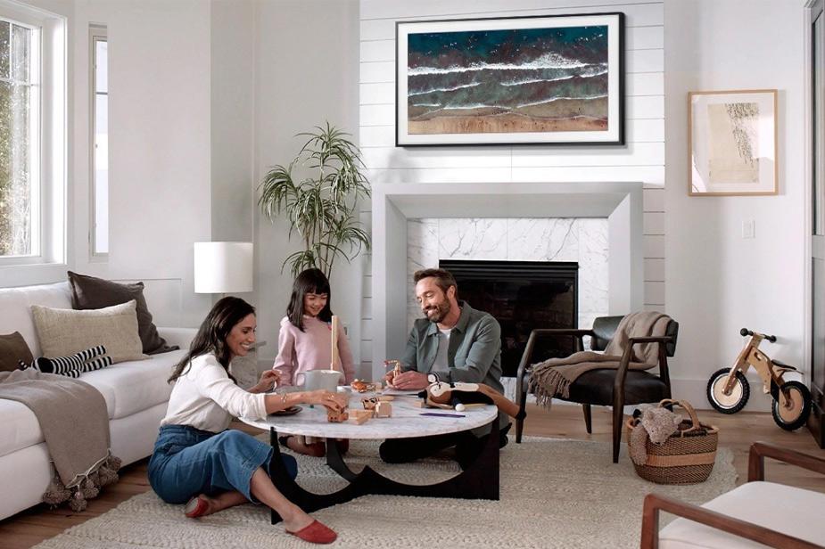Samsung Frame TV u crnom okviru iznad kamina u dnevnoj sobi, ispred koje uz drveni stol sjede majka, otac i djeca