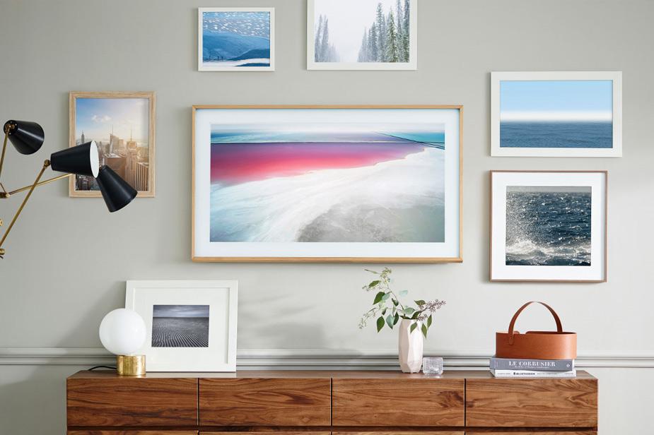 Samsung Frame TV među slikama na zidu iznad drvene komode