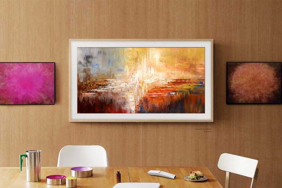 Samsung Frame TV sa svjetlo smeđim okvirom na drvenoj stijeni među slikama u sobi za sastanke