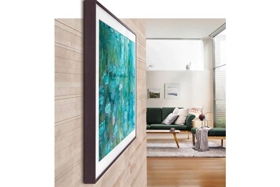 Samsung Frame TV s tamno smeđim okvirom sa slikom Moneta uz pogled na zeleni trosjed